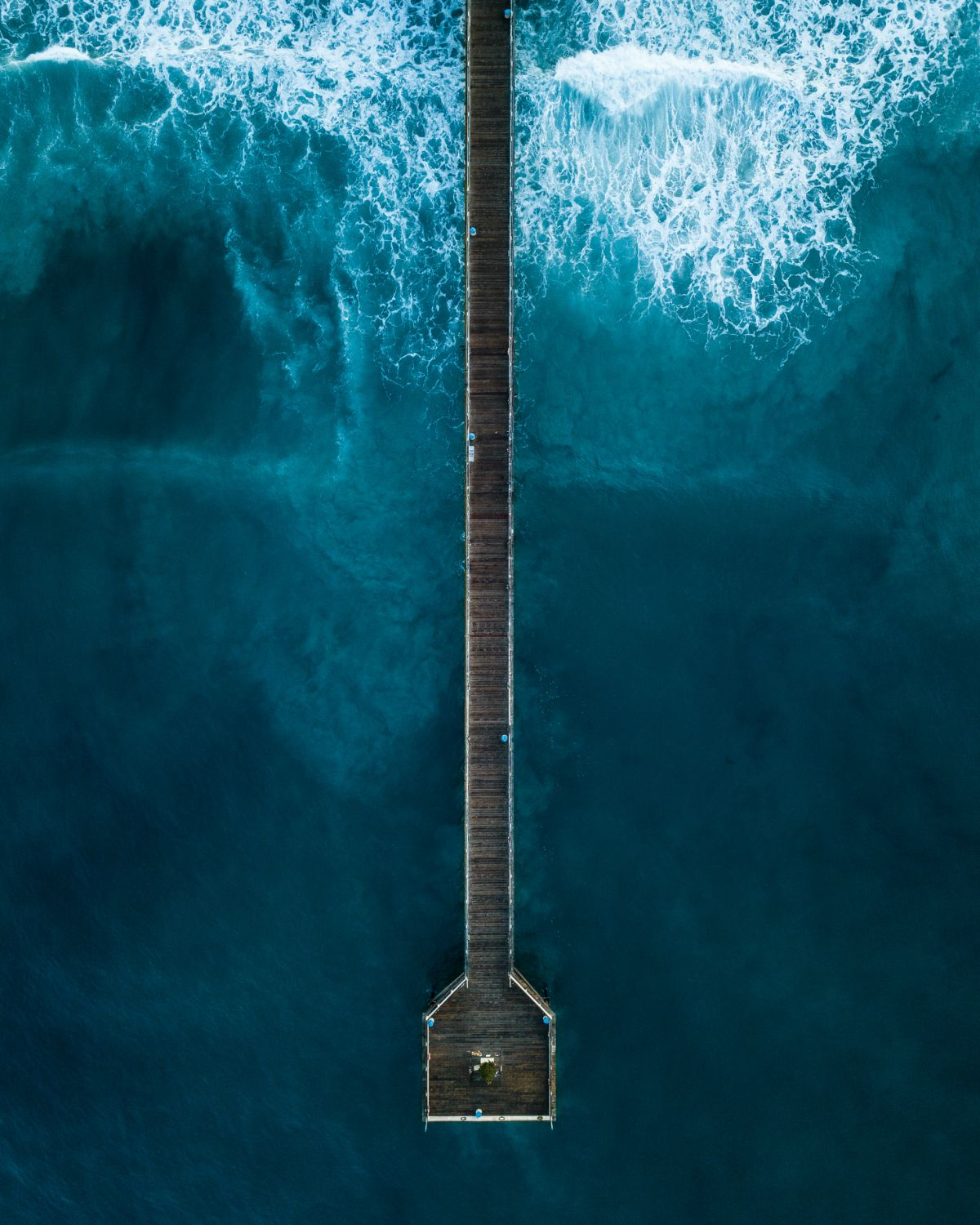 Overheadphoto of a pier on blue ocean